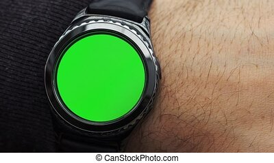 Man hands gestures on a round screen modern smartwatch with a green screen chroma key content