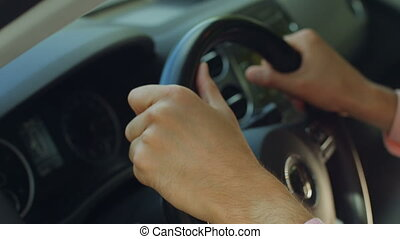 Man hands holding a steering wheel confidently - Close-up of...
