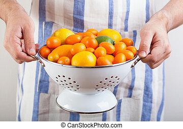 man hands holding colander with citrus fruits