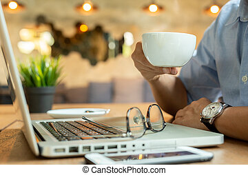 Man hands holding cup coffee with mobile phone and laptop on wooden table.
