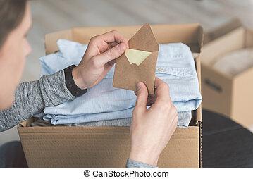 Man hands holding envelope in room