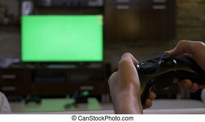 Man hands holding gamepad in front of chroma key green screen plasma display playing video games on console