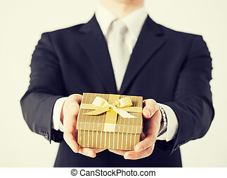 man hands holding gift box - close up of man hands holding...