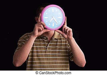 Man hands holding in front of his face a large wall clock showing time