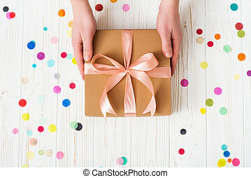 Man hands holding present box with pink bow on white wooden background with multicolored confetti