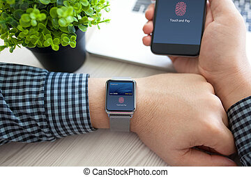 Man hands holding watch phone with debit card touch pay