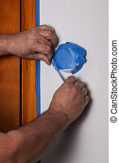 Man hands is covering thermostat with masking tape