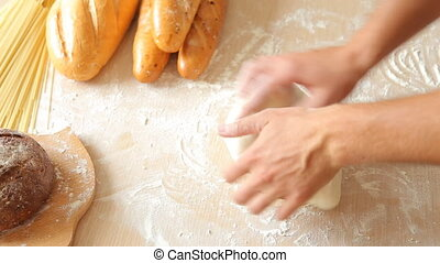 Man hands kneading dough in flour on table.