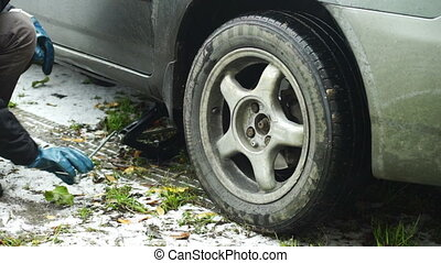 Man hands lifting car up with jack - Changing a car wheel:...