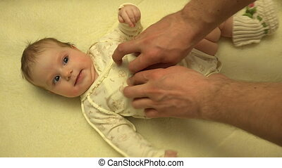 Man Hands Massaging Newborn Baby Body. Closeup