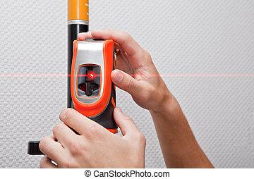 laser level gage - Man hands measuring with laser level gage...