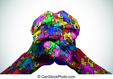 man hands patterned with puzzle pieces of different colors
