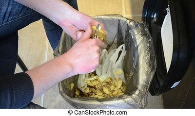 man hands peel potato. paring fall into waste bin.