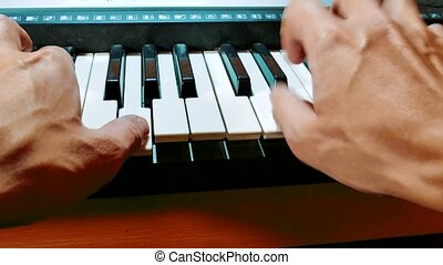 Man hands playing piano. Close-up hands of musician who...