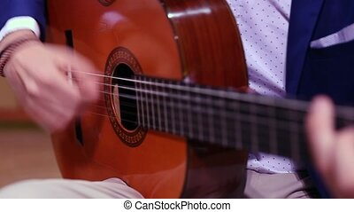 Man hands playing spanish acoustic guitar - Close-up of...