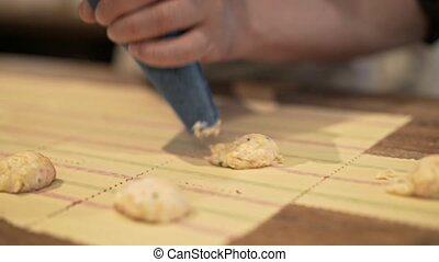 Man hands squeezing tortellini stuffing at home - Hands of...