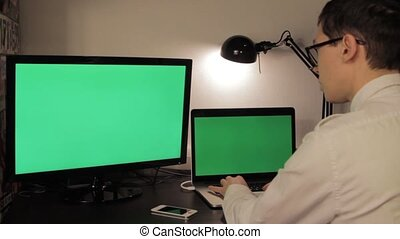 Man hands typing on green screen laptop computer
