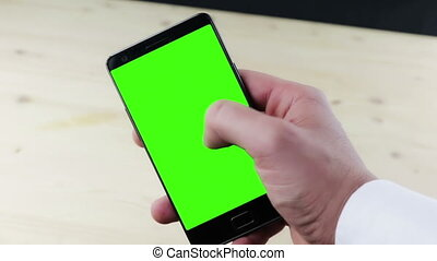 man hands using a smart phone for write text messaging with chroma key, green screen on white background, communication with smartphone technology concept on wood background
