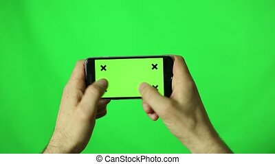 man hands using a smart phone for write text messaging with chroma key, green screen on wood table, communication with smartphone technology concept