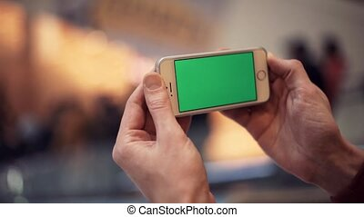 Man hands using smartphone with green display in shopping mall