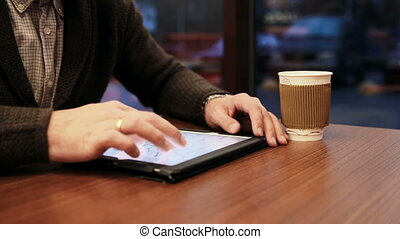 man hands using tablet touchscreen in cafe