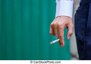 Man hands with cigarette on green background.