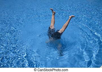 man handstands in a pool