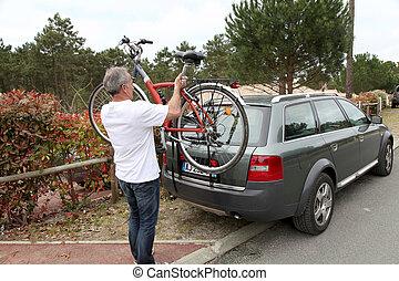 Man hanging bicycle on bike carrier