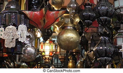 Man using a pole to hang traditional Arabic style lamp in the market of Marrakesh Marrakech.