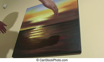 Man hanging seascape sunset oil painting on the wall