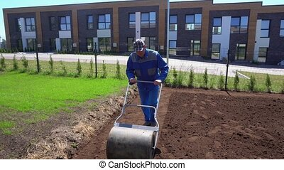 Man Hard Working In Garden with Soil Roller. Gimbal movement...
