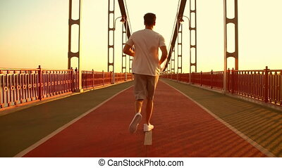 man has a morning jog - back view of a male runner. guy...