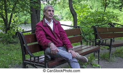 Man has a rest on a bench on the be