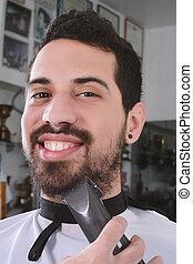 Man having a beard cut with hair clippers.