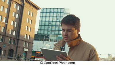 Man having a city walk with tablet computer - Steadicam shot...