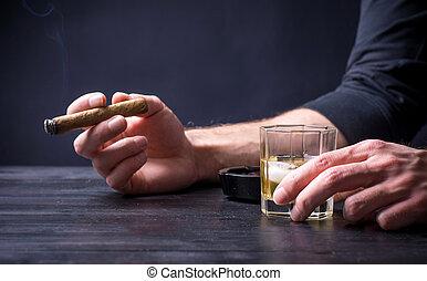Man having a drink and smoking at a bar