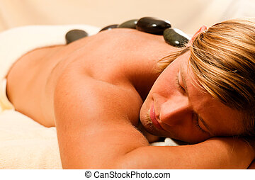 man having a hot stone therapy session