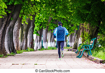 man having a morning run on alley of Kiev embankment in...