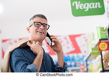 Man having a phone call at the supermarket