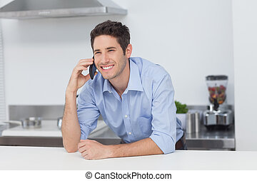 Man having a phone conversation in the kitchen