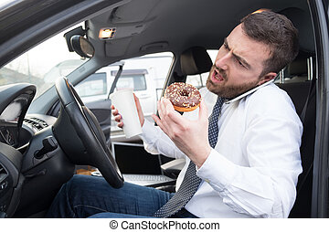 Man having breakfast and driving seated in car - Man having...