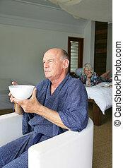 Man having breakfast in front of a window