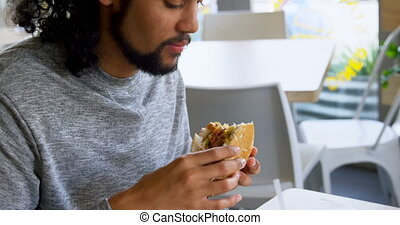 Man having burger in cafe 4k - Side view of man having ...