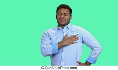 Man having chest pain on color background. Young dark-skinned man suffering from heart ache. Heart disease concept.