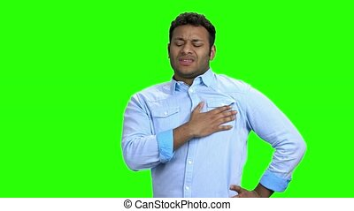 Man having chest pain on green screen. Young man suffering...