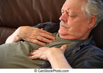 Man having chest pain on sofa