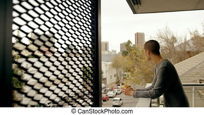 Man having coffee while standing in balcony 4k - Man having ...