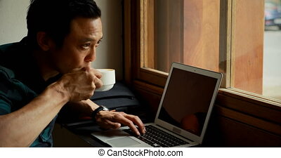 Man having coffee while using laptop 4k