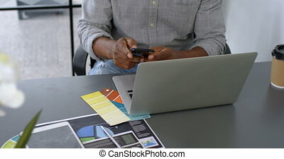 Man having coffee while using mobile phone on desk 4k
