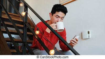 Man having coffee while using mobile phone on stair 4k - Man...